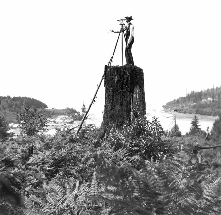 A surveyor atop a stump at the soon-to-be Fort Lawton