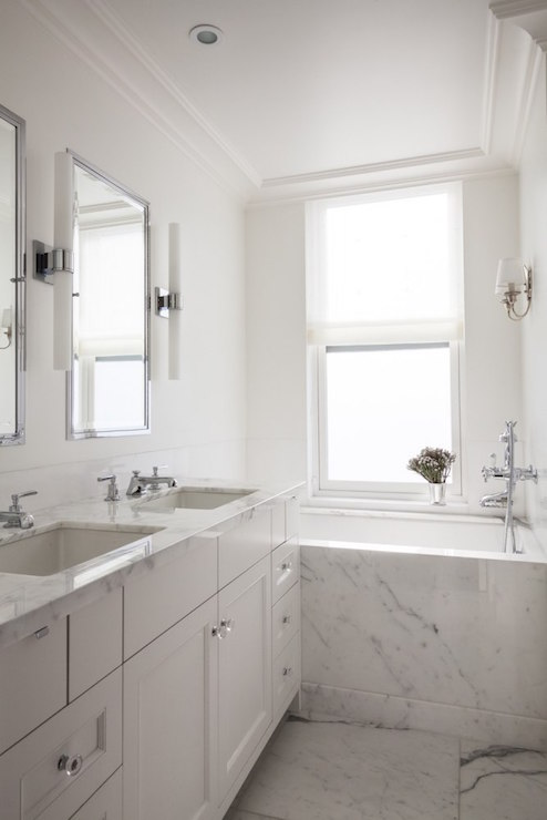 Polished natural marble slab countertops over custom designer cabinetry in bathrooms