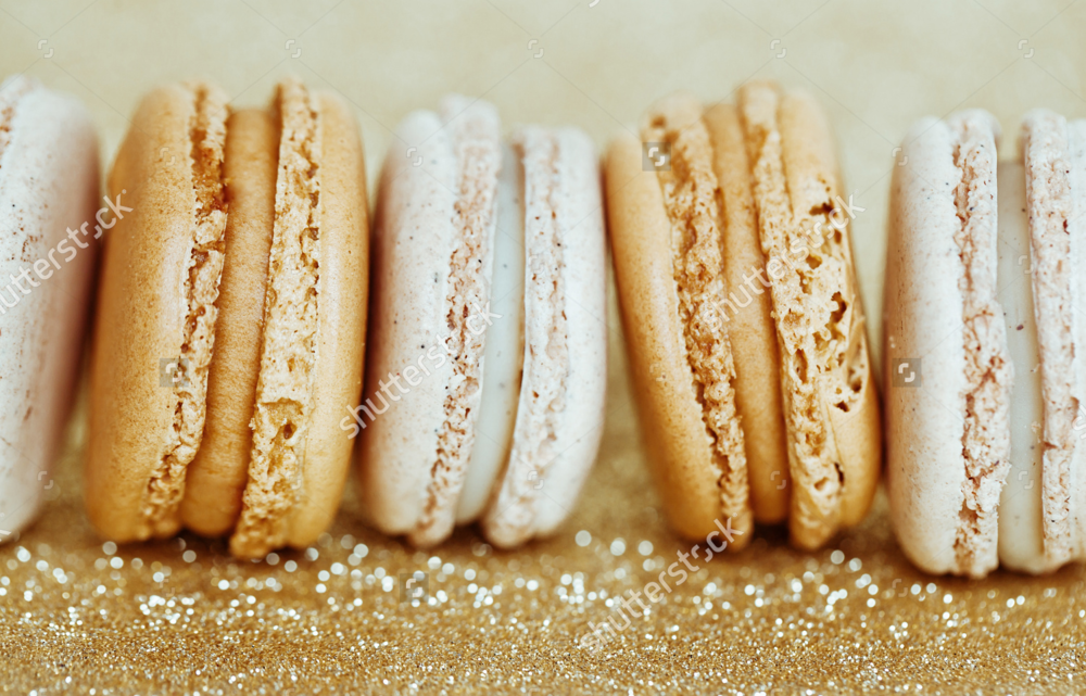 stock-photo-luxury-vanilla-and-caramel-macaroons-on-gold-background-181704647.jpg