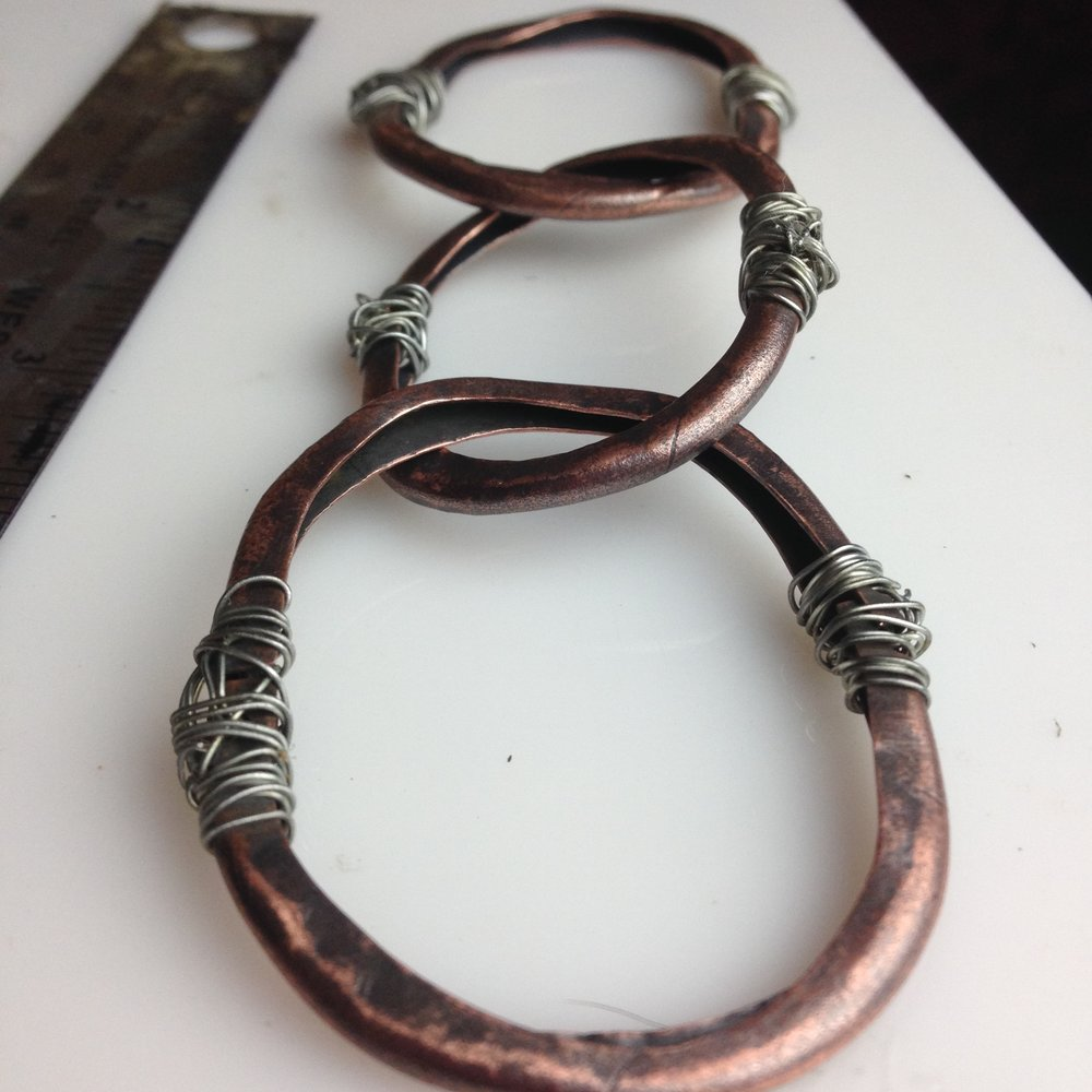 Each copper link in the chain was made from a flat piece of copper sheet which I formed into hollow round shapes then sewed together with wire.