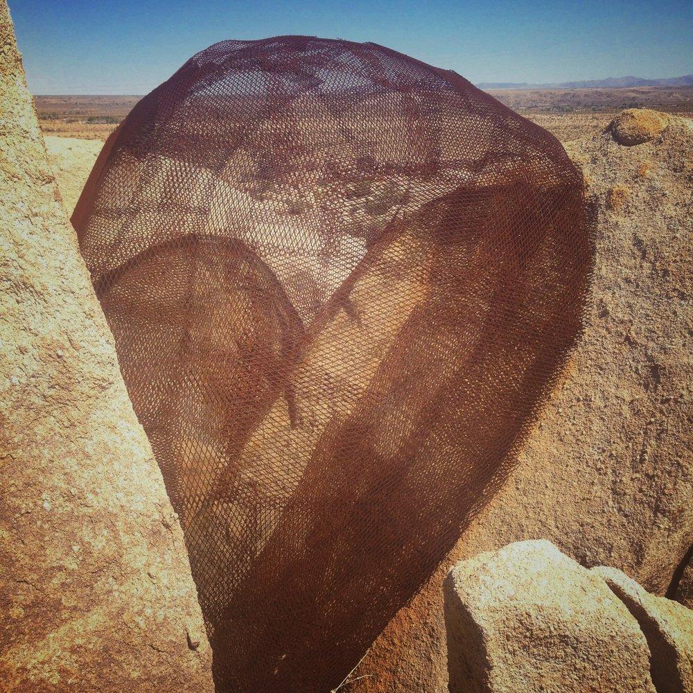 #heartshapedworld metal cage embedded in rocks near Joshua Tree, CA