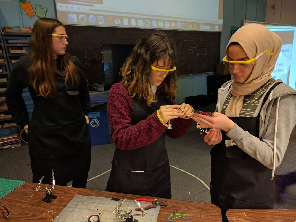 Roni, Marie and Madeeha soldering an LED array.