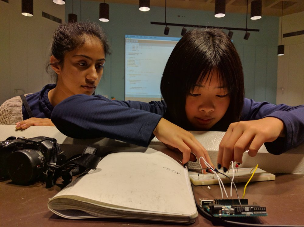 "Simran and Ally work at implementing their ""Status Prism"" design's circuits."