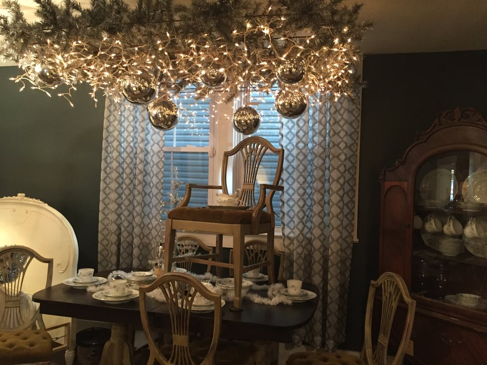 This room got a gorgeous upgrade. We hung a rusty old grate above the table and filled it with icicle lights and greens. So pretty!