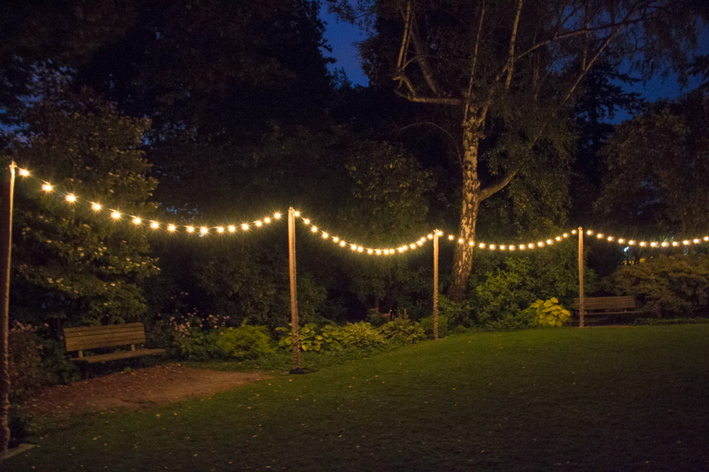 String lighting, upright posts with burlap pole covers