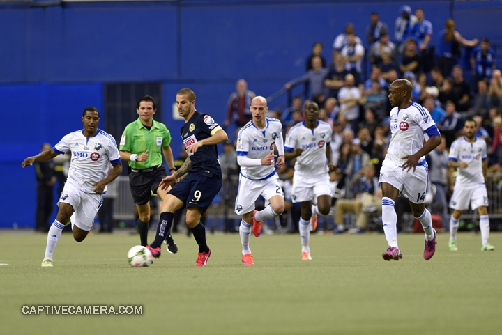 Montreal, Canada - April 29, 2015: Dario Benedetto #9 of Club America is immediately surrounded by Montreal Impact players.