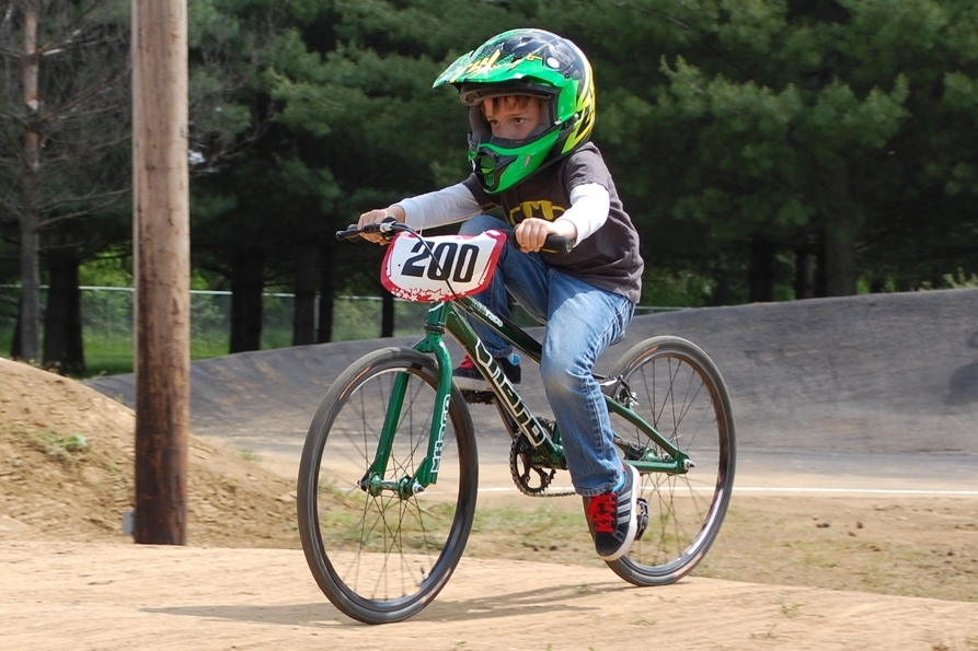 A new racer takes laps in the required helmet, long sleeves and long pants.