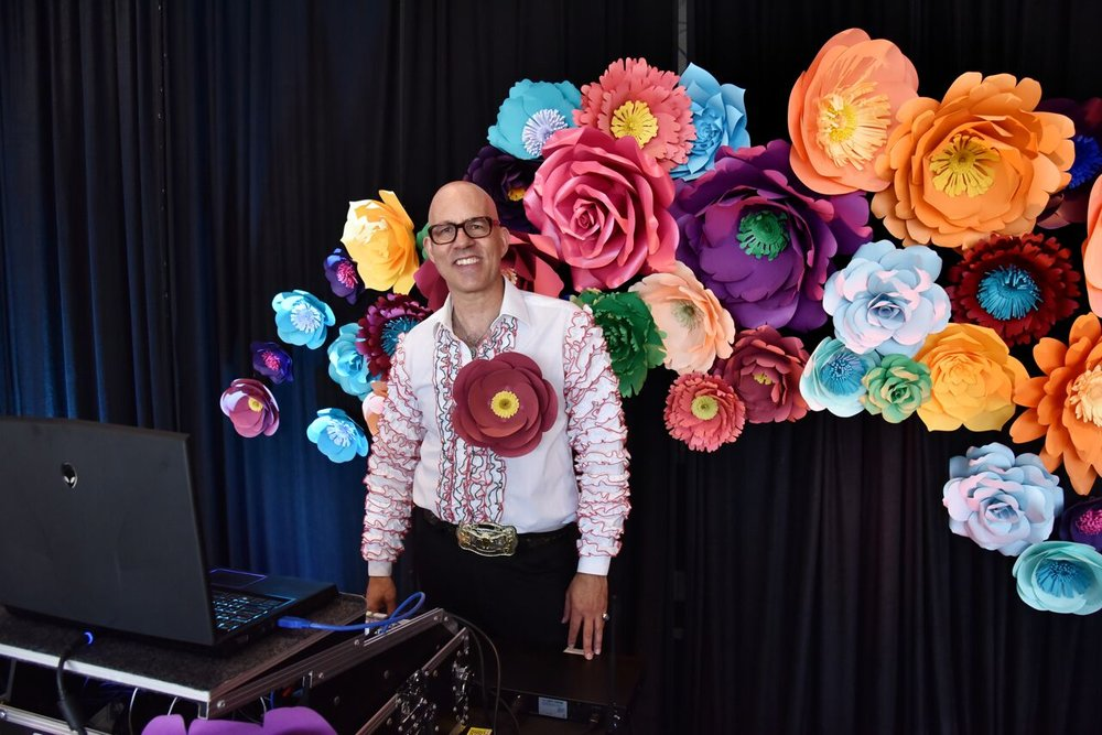 DJ Senor Amor throwing down some latin flare in front of a wall of paper blooms by The Bleu Dahlia.