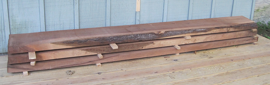 A small stack of walnut lumber that has been air drying