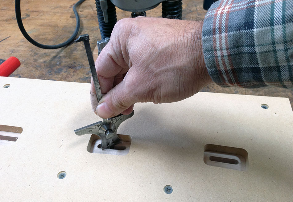 Checking the depth of the slat mortises before removing the leg from the jig