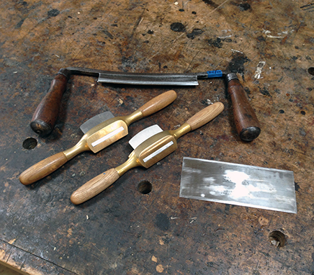 A chairmaker's toolkit— drawknife, flat bottom spokeshave, round bottom spokeshave, and card scraper