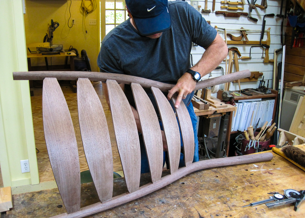A student is fitting slats for a walnut rocking chair