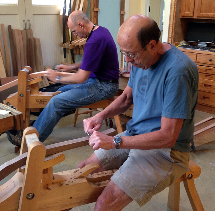 Two students shape the relief cut on the rear legs at the end of day one of class