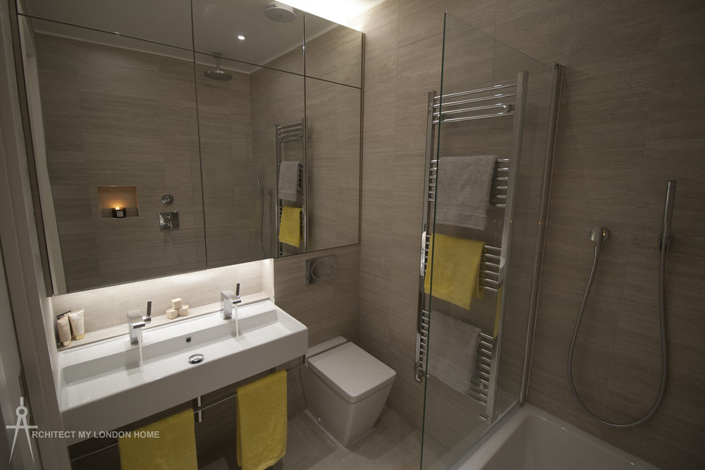 Luxurious bathroom with double vanity, soft closing wc, bath, ceiling and hand-shower and demister pads in the mirrored bespoke built wall unit