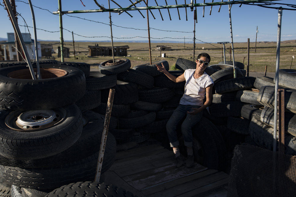 Eileen poses for a portrait inside her tire fort outside of one of her properties in Cisco, Utah. Eileen is restoring many of the old buildings and putting them on Airbnb for people to rent in the hopes of bringing the town back.