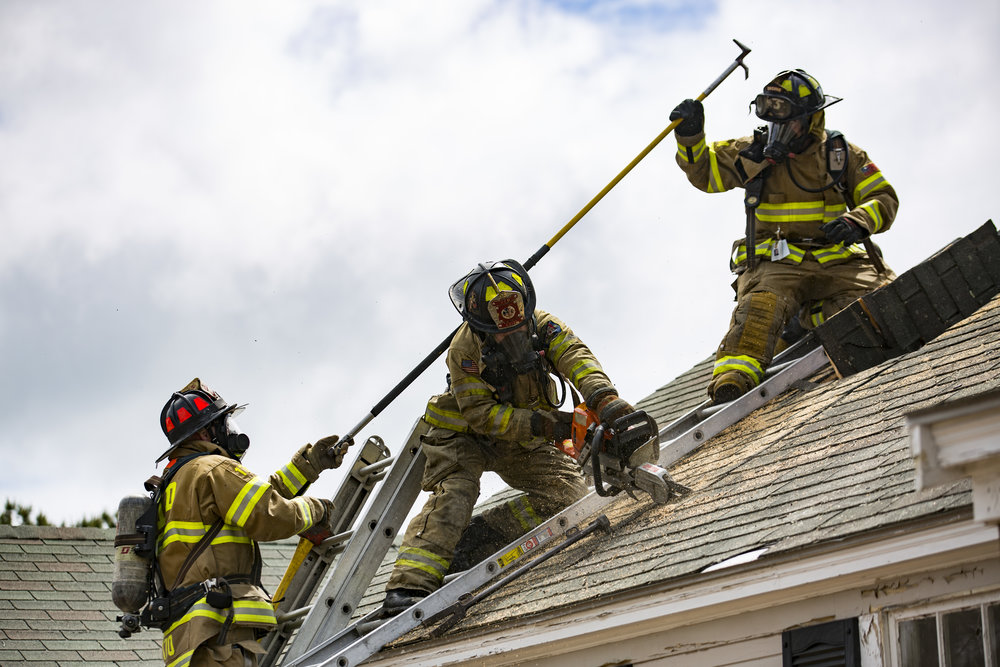 "Yarmouth Fire Lt. Scott Smith instructs Ted Miller and Kai Raiskio while they practice removing parts of a roof at the Cavalier Motor Lodge on Route 28 on June 7, 2017. The abandoned motel, which is scheduled to be demolished later this month, provides a unique opportunity for training Smith said. ""It's actually realistic, hands-on type training,"" he said."