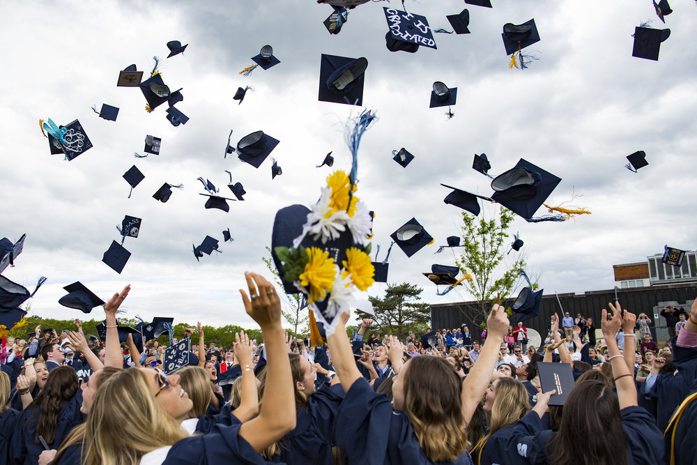Sandwich High School students throw their caps into the air at the end of the graduation ceremony on June 3, 2017.