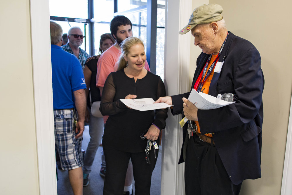 Client Mark Curran greets guests and hands out maps during the Community Connections new building grand opening on June 21, 2017.