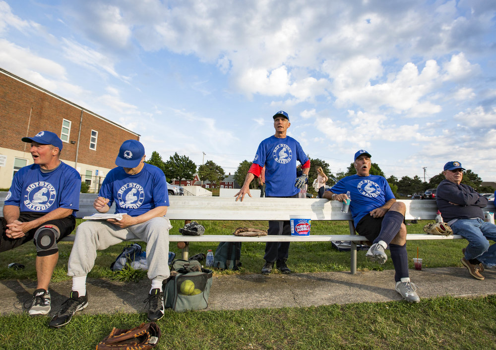 Stephen Akerman, center, watches his teammates of the Hot Stove Saloon from the bench during their game against the Mid-Cape Door on June 27, 2017. Akerman is the youngest player in the league at 56.