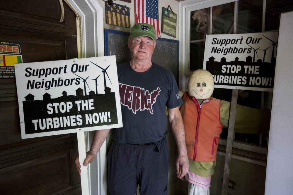 Barry Funfar poses for a portrait with his anti-turbines signs at his home in Falmouth, Massachusetts on July 3, 2017.
