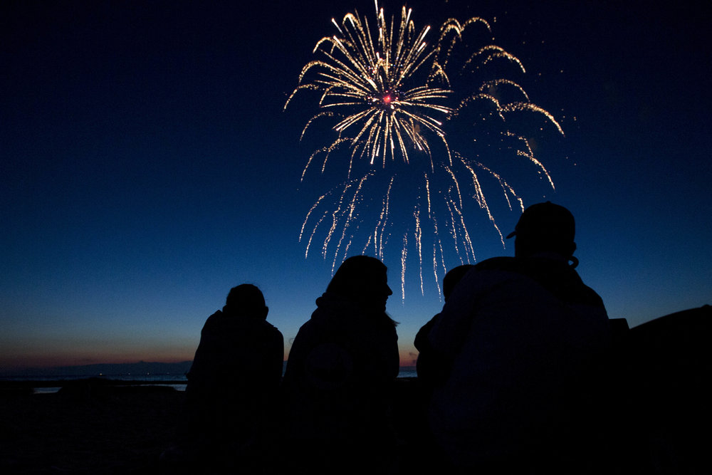 The Lulley family watches the fireworks on the shore of Rock Harbor in Orleans, Massachusetts on July 2, 2017.