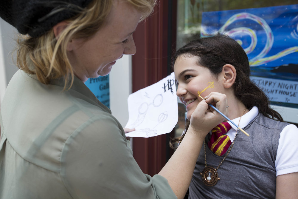 Haley Rae Smith paints a flying key on Julie DaSilva's, age nine and daughter of Sandro DaSilva, face outside of The Cape Cod Art Bar during the Harry Potter themed scavenger hunt in the Mashpee Commons on July 8, 2017.