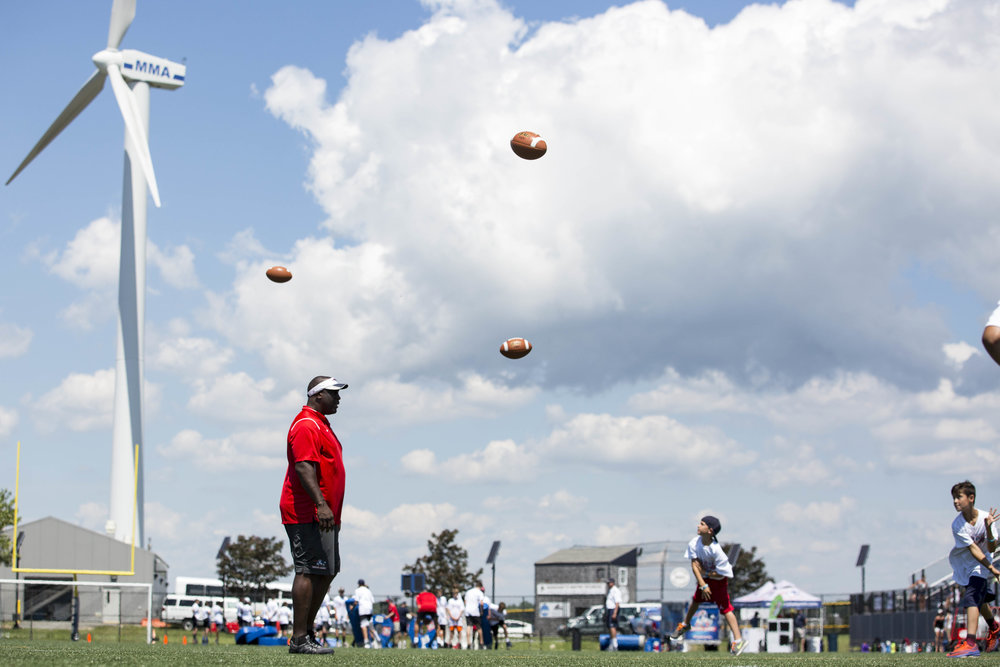 Balls fly over the head of former New England Patriots star Vernon Crawford during a passing drill a the Football for YOU clinic held at Massachusetts Maritime Academy on July 10, 2017.