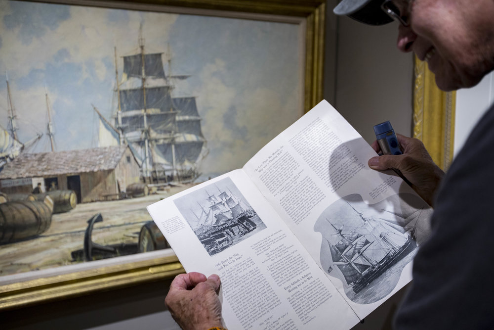 Don Stucke, the Maritime Museum curator, compares a photograph in a 1936 Cape Cod Chamber of Commerce publication to a painting in the museum. Karl Hoffman found the publication while looking for records of his grandfather's restaurant on the Cape.