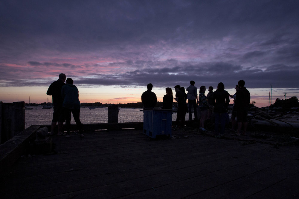People watch the sunset from the dock by the Woods Hole Science Aquarium on July 29, 2017.