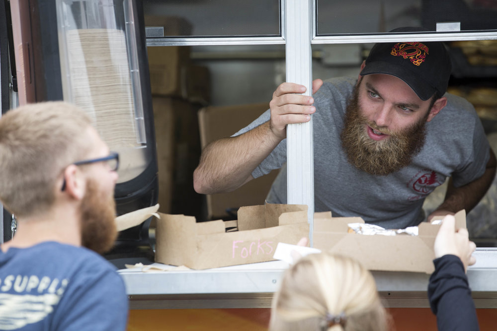 Cape Cod Times reporter Ethan Genter serves food to Josh Kilmonis and Elizabeth Prest from the GottaQ Barbecue food truck on August 12, 2017.