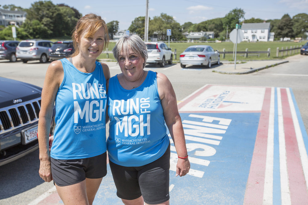 Cancer survivor Suzanne Sarafin and her running partner, Lee Macleod pose for a portrait at the Falmouth Road Race finish line on August 16, 2017.