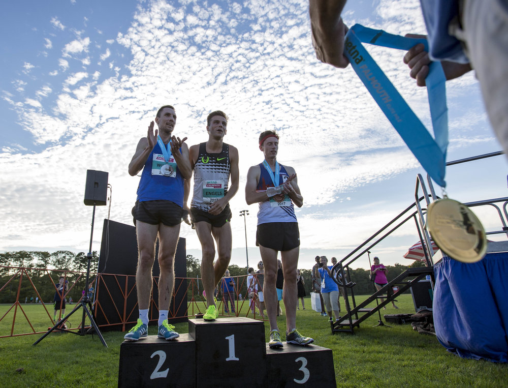 Craig Engels steps up to accept his first place metal next to Nick Willis and Colby Alexander after winning the men's Aetna Falmouth Elite Mile on August 19, 2017.