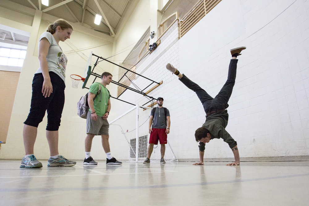 From left to right: Emily Schueller, Logan Mosher and Nick Sahagian watch Seth Baker as he does a handstand in Ping Center on September 22, 2017. Baker, Schueller, Mosher and Sahagian recently discovered Baker is a break-dancer and asked him to show off his skills during the middle school service tour.
