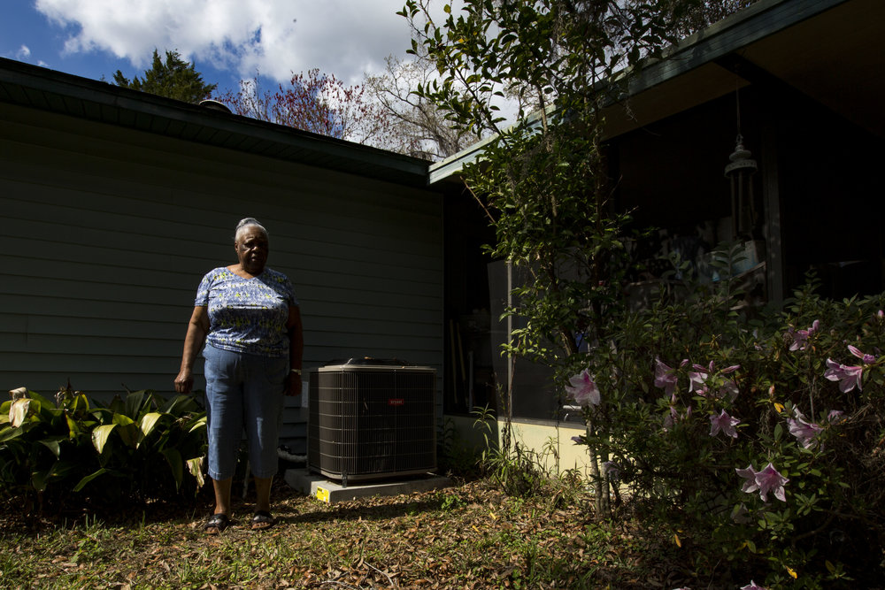 Fannie McCray poses for a portrait in her backyard in front of her new HVAC system on February 20, 2018. McCray was unaware the assessment was going to be attached to her property tax bill and is in jeopardy of losing her home.