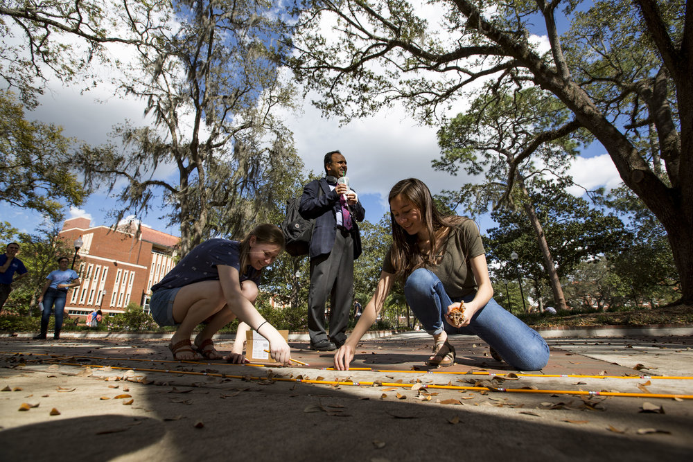 University of Florida students Robyn Natherson and Tanya Martin lay pencils on the ground while professor Anil Rao oversees them during an attempt to to break a world record for the longest line of pencils in succession in the Plaza of the Americas on February 23, 2018.