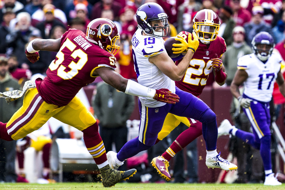 Vikings wide receiver Adam Thielen runs between two Redskins players during the Washington Redskins home game against the Minnesota Vikings on November 12, 2017. The Redskins lost 30-38 to the Vikings.