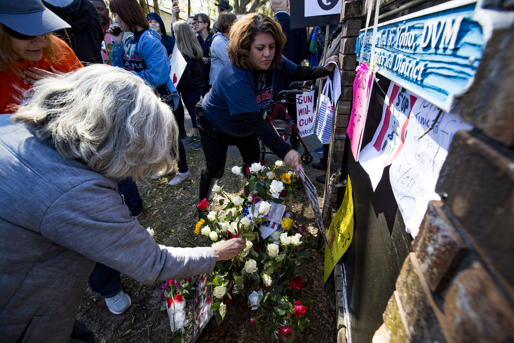 People place signs and flowers against Congressman Ted Yoho's office sign during a protest on March 14, 2018. Students across the country walked out of school in a nationwide demonstration on the one month anniversary of the shooting that killed 17 people at Marjory Stoneman Douglas High School in Parkland, Florida.