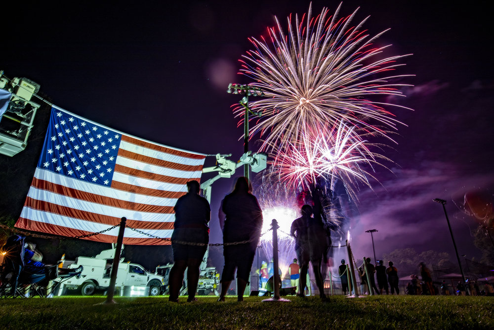 """A giant American flag hangs by the stage as people watch fireworks show at the Alachua Fourth of July Celebration at the Hal Brady Recreation Complex on Wednesday. Alachua's firework display has been dubbed the """"Largest Small Town Fireworks Display in America."""""""