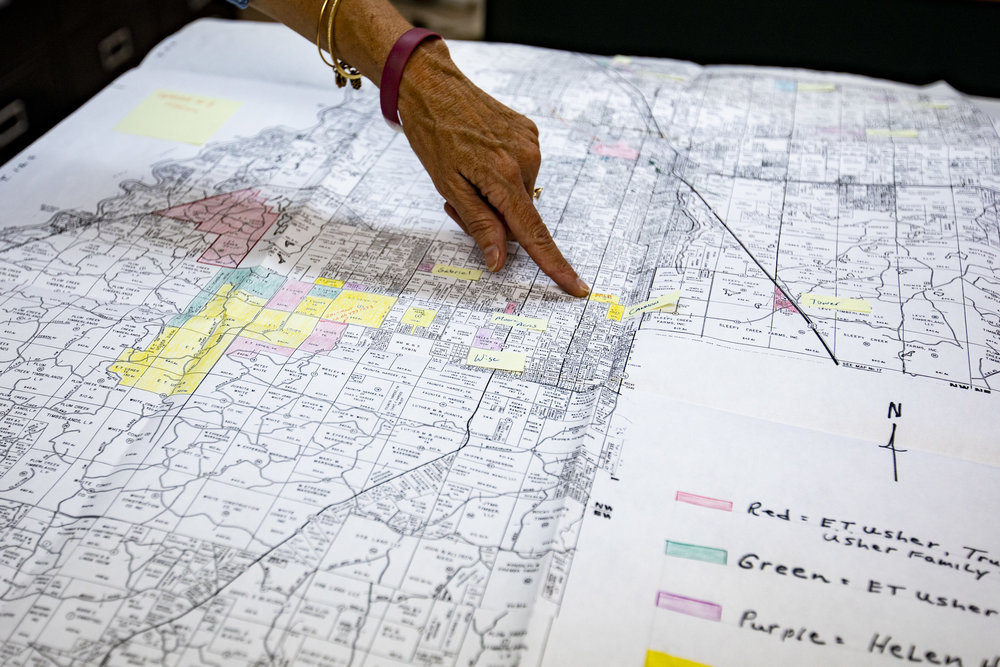 Lynetta Usher Griner points to spots of land that Usher Land & Timber, Inc. owns on a map of Levy County.