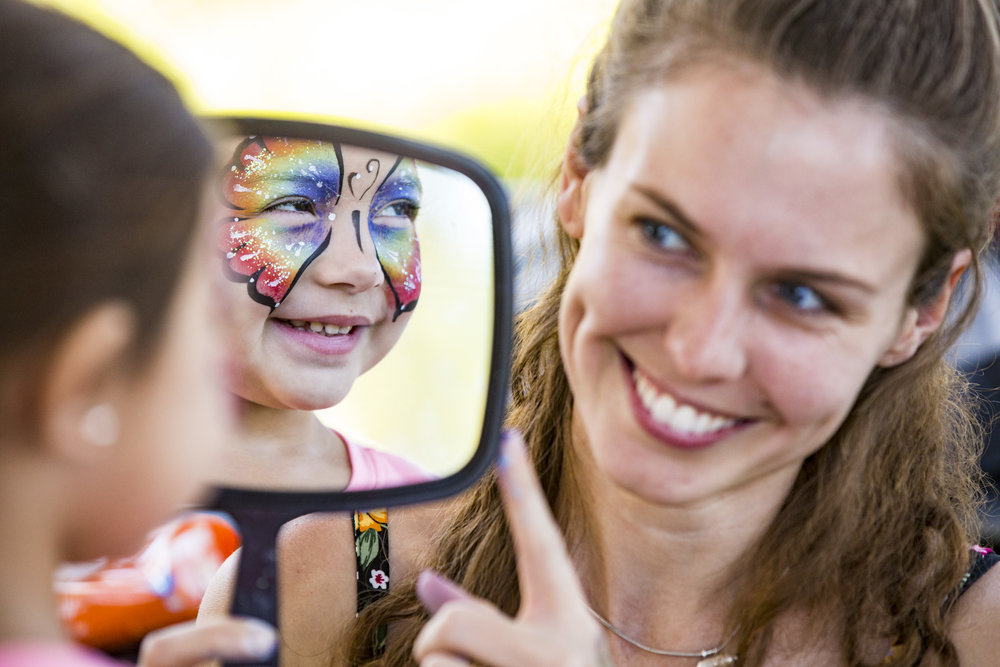 Sophia Brumfield, 4, reacts to her reflection after getting her face painted by Leela Woodham of Easyjourney Entertainment during the 13th annual Butterfly Festival at the Florida Museum of Natural History on October 13, 2018.