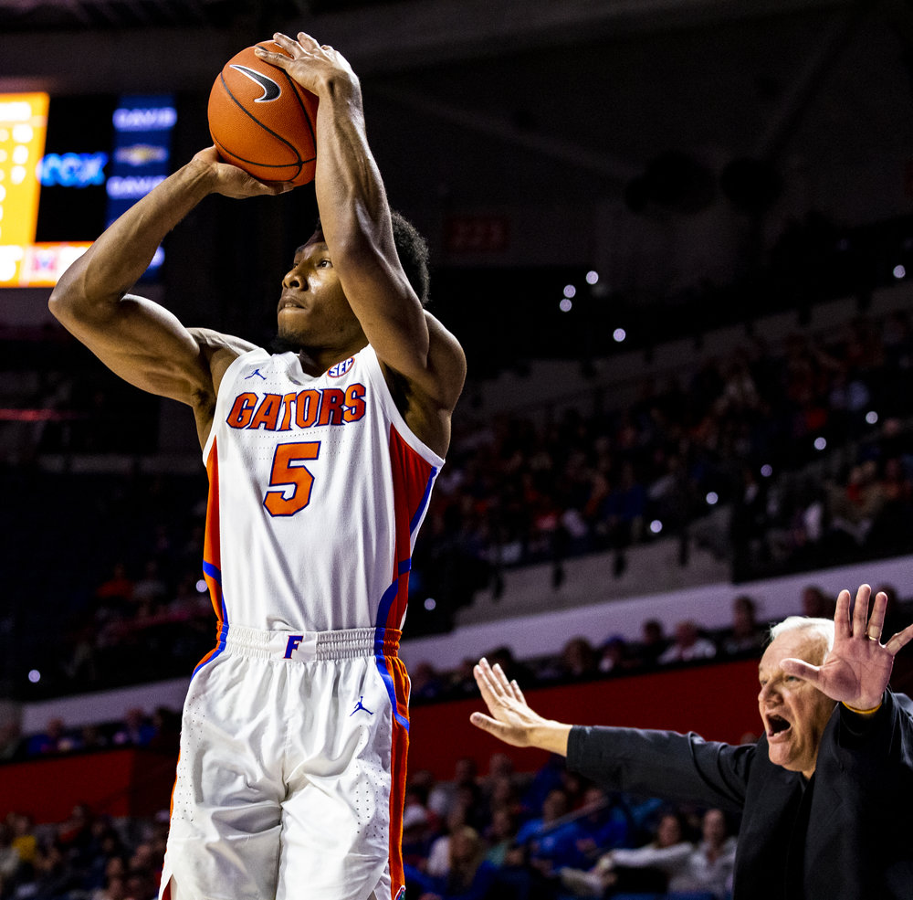 Florida Gators guard KeVaughn Allen (5) shoots a three-pointer as Mercer Bears head coach Bob Hoffman yells behind him during the Florida Gators home game against the Mercer Bears on December 18, 2018. The Florida Gators won 71-63.