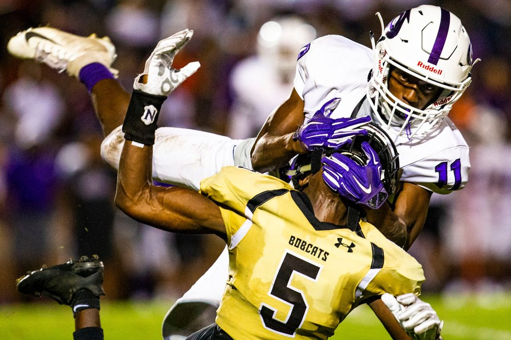 Gainesville Hurricanes defensive back Earl Jefferson (11) grabs Buchholz Bobcats wide receiver Isaiah Michel (5) face mask during the city rivalry game at Citizens Field on October 5, 2018. The Buchholz Bobcats beat the Gainesville Hurricanes 27-7.