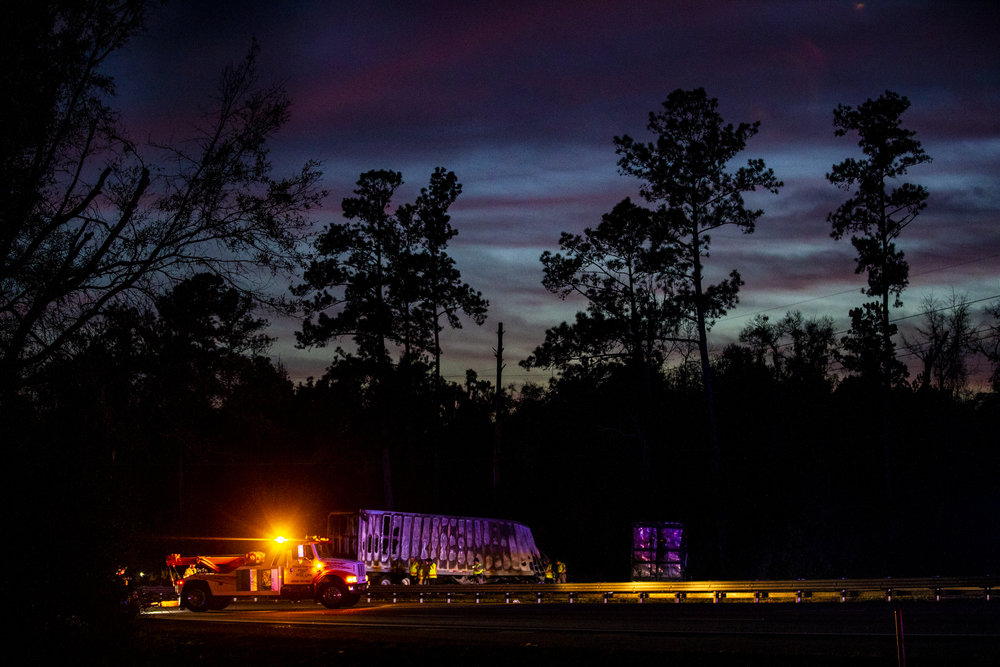 The sun sets over burned semi-trucks and car debris after a wreck with multiple fatalities on Interstate 75 on January 3, 2019. Seven people died and at least eight more were injured, some of them critically, in the multi-vehicle crash.