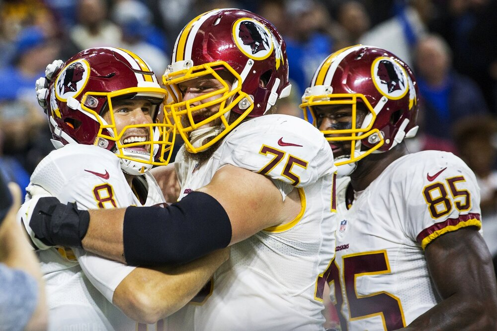 Washington Redskins quarterback Kirk Cousins hugs his teammates after scoring a touchdown during the Redskins vs Lions game at Ford Field on October 23, 2016.
