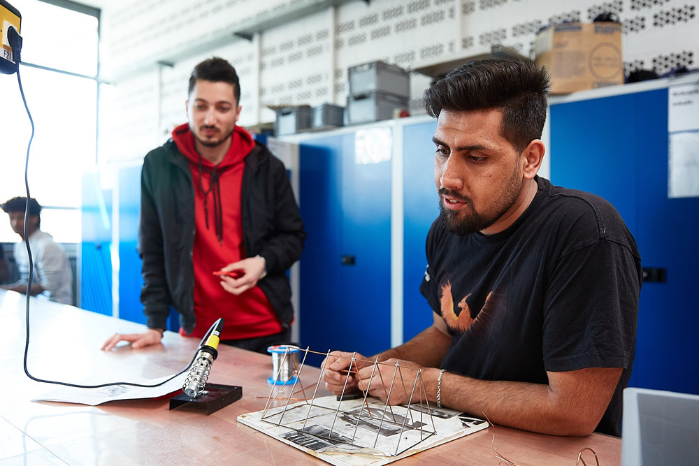 Kosai Alsaleh (left), a second-year integration class student from Raqqa, Syria, at the Franz Oberthür Vocational School in Würzburg, works on a soldering project in a metalworking course with a colleague from Afghanistan