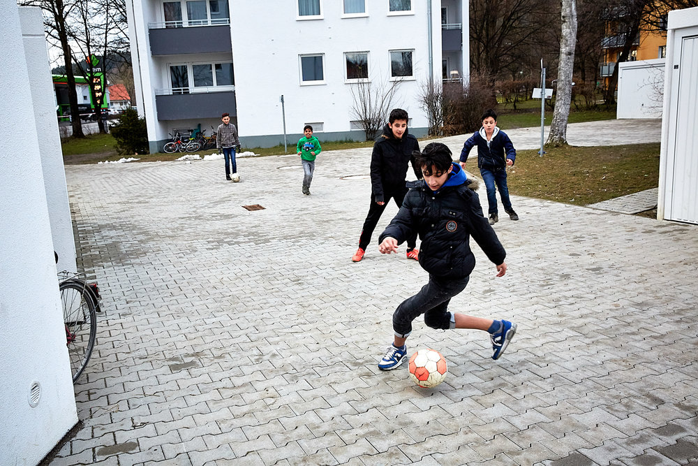 Children play soccer outside of a dedicated refugee housing apartment building in Kaufbeuren