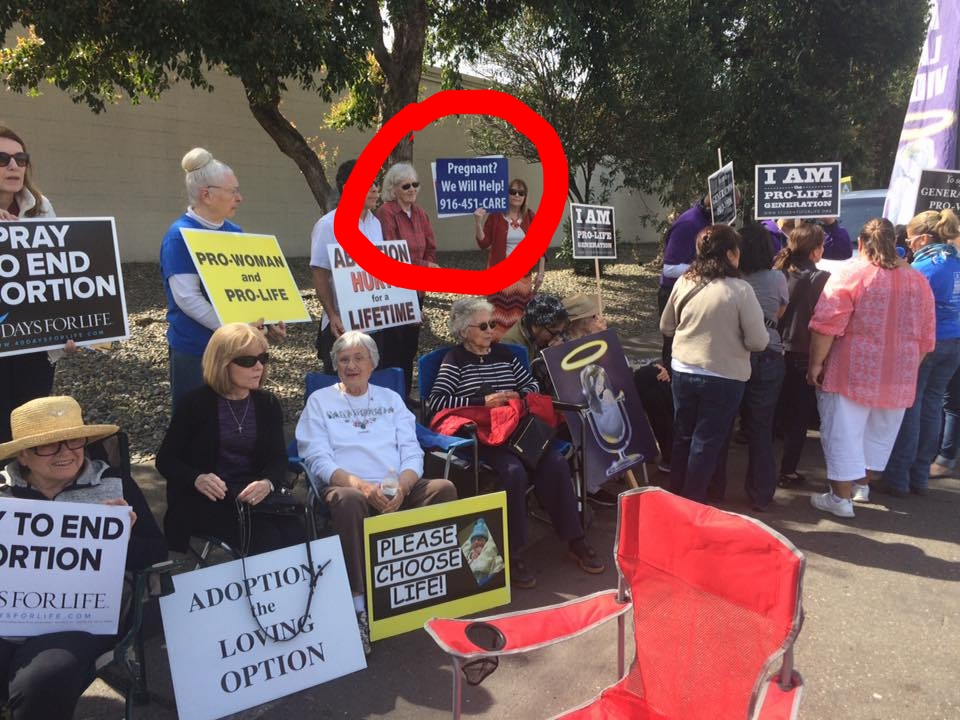 A protester holds a sign with Sac Valley Pregnancy Clinic's phone number, as they gather in the street across from a now closed Sacramento health clinic. The former all options clinic provided free adoption services, pre-natal referrals, abortion services and cancer screenings.  Source:  40 Days for Life Sacramento Facebook page