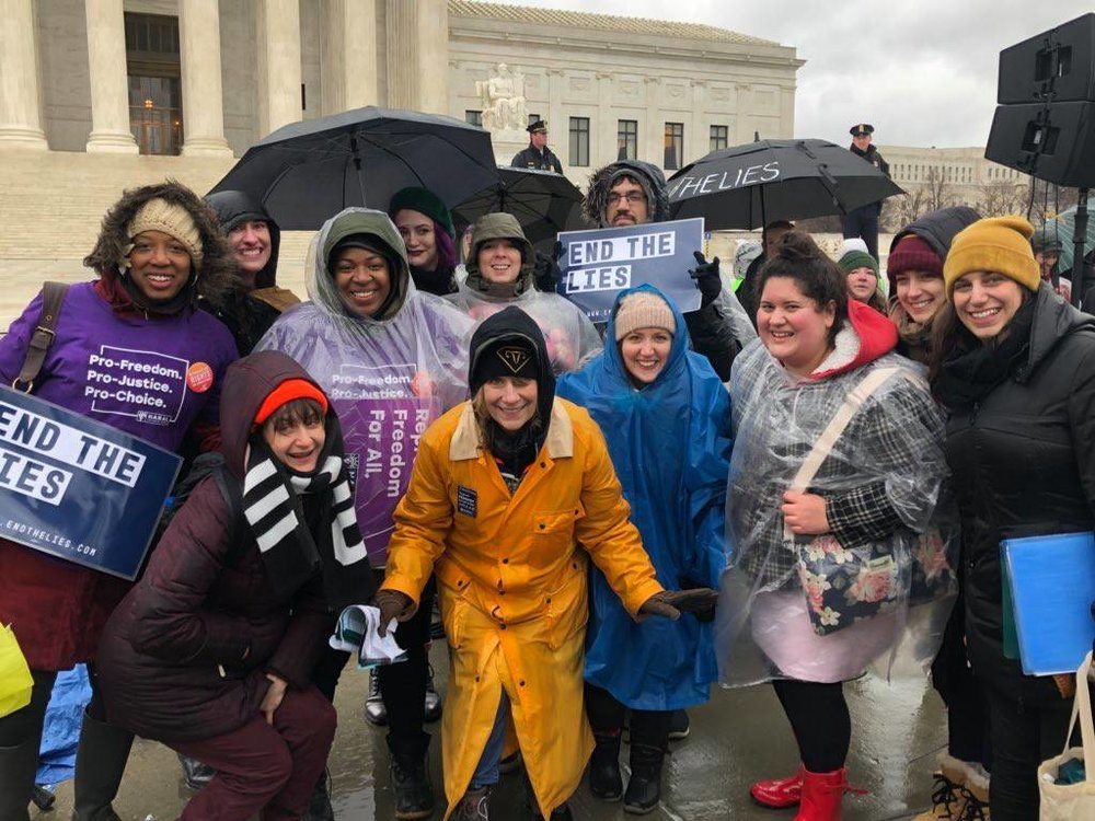 Lady Parts Justice League's  Lizz Winstead  (in yellow slicker) led the rain-drenched, high energy rally in front of the Supreme Court on Tuesday.