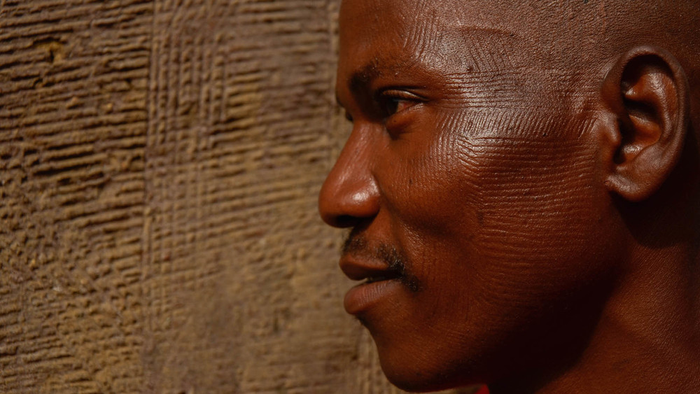 Betamaribe men with traditional patterns in his face that match the ones on the walls of his house in Northern Benin.