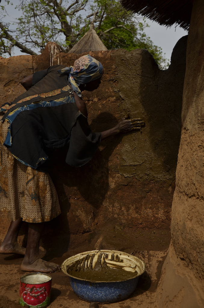 A woman rendering her house with cow dung in Northern Benin.